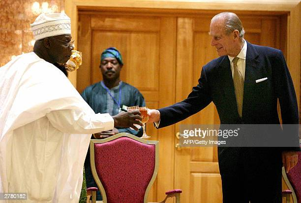 Nigerian President Olusegun Obasanjo toasts with Prince Philip Duke of Edinburgh during a reception in honor of Britain's Queen Elizabeth II at the...