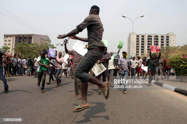 Nigerian protesters march towards the secretariat of the Nigerian Bar Association during a protest in Abuja over the suspension of Chief Justice of...