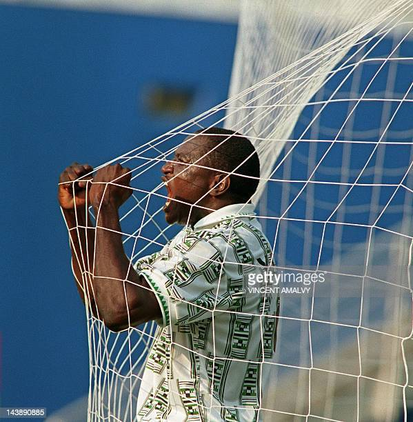 Nigerian Rashidi Yekini screams 21 June 1994 through the net after scoring the first goal at the Cotton Bowl in Dallas during their World Cup match...