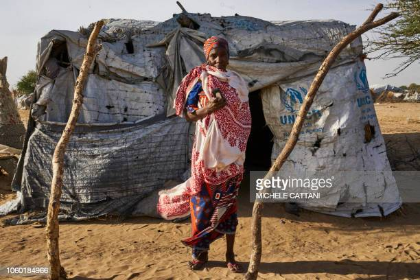 TOPSHOT Nigerian refugee Aicha Younoussa poses with a smartphone in front of her tent in Bol on November 8 2018 Due to Boko Haram's threat Aicha and...