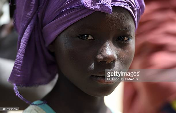 A Nigerian refugee girl poses at a Chadian gendarmerie camp in the village of Klissoum near N'Djamena on March 28 2015 Two months after neighbouring...