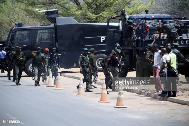 Nigerian security forces take position as students protest outside the South African Digital Satellite TV's Nigerian headquarters in Abuja against...
