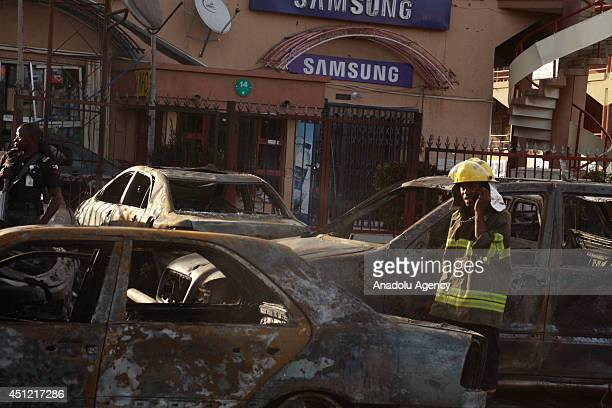 Nigerian security officials inspect the site of a blast in Abuja Nigeria on June 25 2014 At least 21 people were killed when an explosion rocked a...