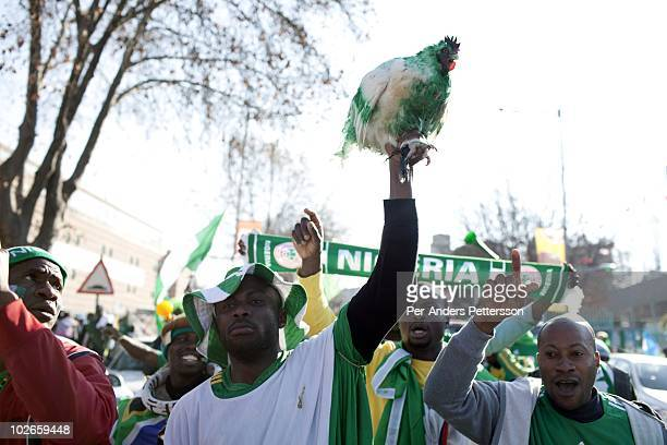 Nigerian soccer fans carry a live chicken to a game between Nigeria and Argentina on June 12 2010 outside Ellis Park stadium in Johannesburg South...