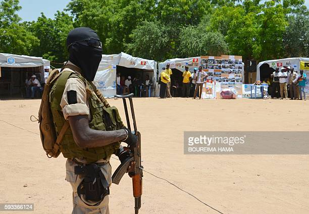 Nigerian soldier stands guard near information stands in a camp for internally displaced people home to some 300000 Nigerian refugees and internally...