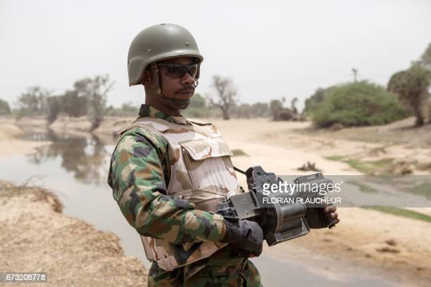 A Nigerian soldier with a grenade launcher stands guard near the Yobe river that separates Nigeria from Niger on the outskirt of the town of Damasak...