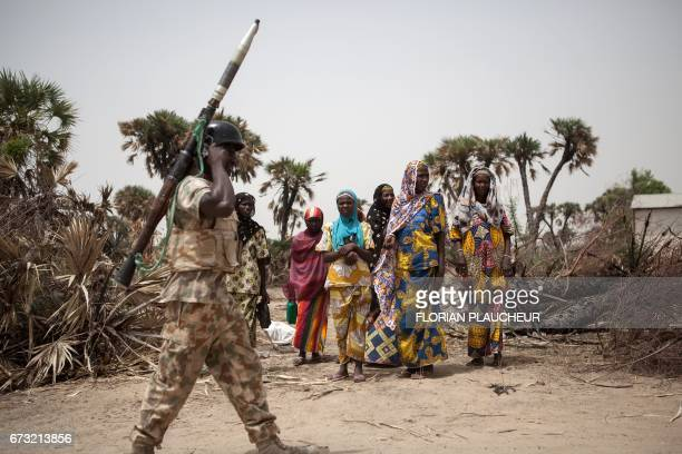 A Nigerian soldier with a rocket propelled grenade patrols on the outskirt of the town of Damasak in North East Nigeria on April 25 2017 as thousands...