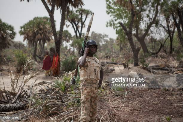 A Nigerian soldier with a rocket propelled grenade stands guard on the outskirt of the town of Damasak in North East Nigeria on April 25 2017 as...