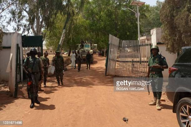 Nigerian soldiers and police officers stand at the entrance of the Federal College of Forestry Mechanisation in Mando, Kaduna state, on March 12...