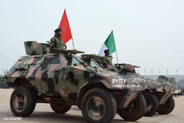 Nigerian soldiers stand on armoured vehicles during a parade marking the country's 58th anniversary of independence on October 1 on Eagle Square in...