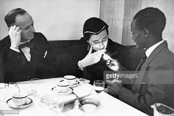 A Nigerian student lights a cigarette for Patricia Farrier of South Africa at a London restaurant February 1955 Farrier who has left her native...