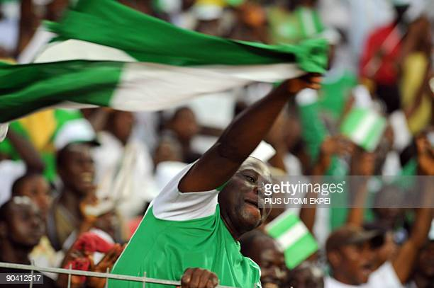 A Nigerian supporter celebrates with flag as his team leads Tunisian during the World Cup qualification match in Abuja Sunday on September 6 2009...