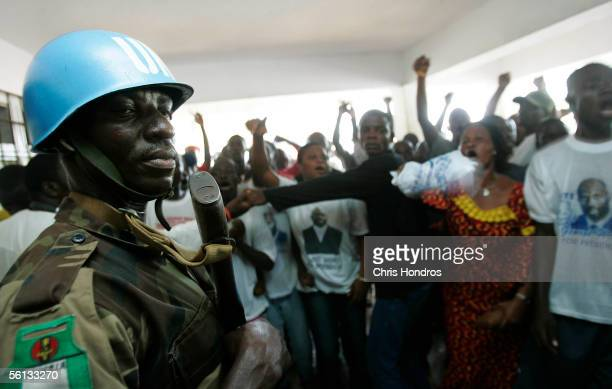 Nigerian United Nations peacekeeper stands guard while supporters of presidential candidate George Weah protest outside of Weah's party headquarters...