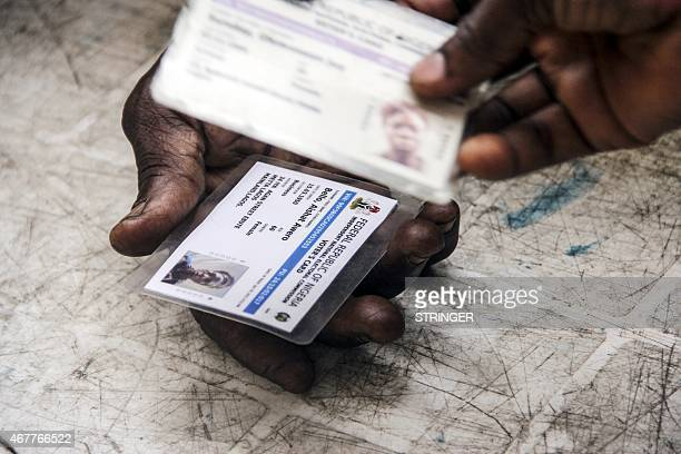 A Nigerian voter returns on March 27 2015 his old electoral card in exchange of a new one prior to the Presidential poll on March 28 in Lagos...