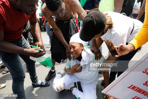 Nigerian woman based in South Africa weep as others comfort her during a protest outside their embassy in Pretoria on October 21, 2020 in solidarity...