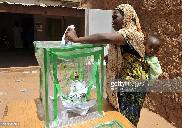 A Nigerian woman carrying her baby casts her vote at a polling station during the presidential elections in Daura on April 16 2011 Nigerians turned...