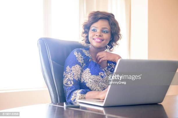 Nigerian woman in office with laptop looking away