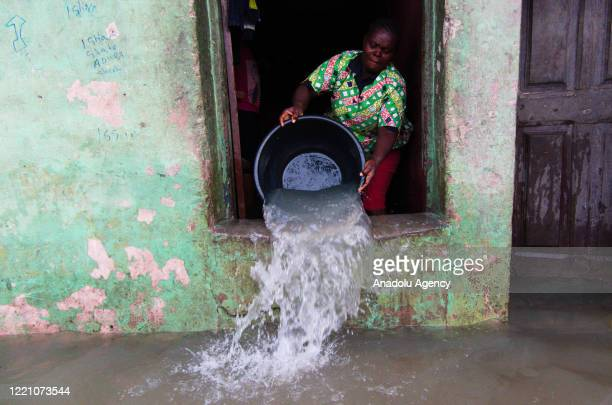 Nigerian woman removes water from her house after heavy rains caused flood in Lagos, Nigeria on June 18, 2020.