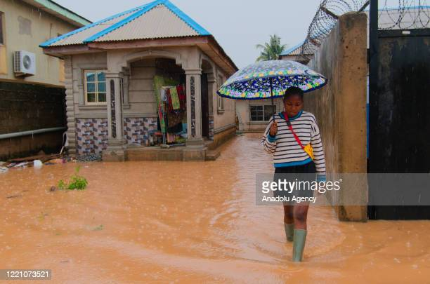 Nigerian woman walks at a flooded place after heavy rains hit Lagos, Nigeria on June 18, 2020.