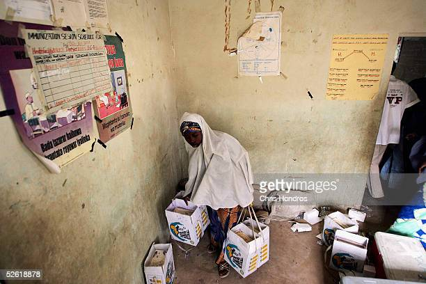 Nigerian woman working as doortodoor innoculator gathers her day's supply of oral polio vaccine before canvassing an urban neighbourhood during a...