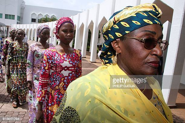Nigerian Women's Affairs minister Hajia Aisha alHassan leads the 21 Chibok girls who were released by Boko Haram last week as they arrive on October...