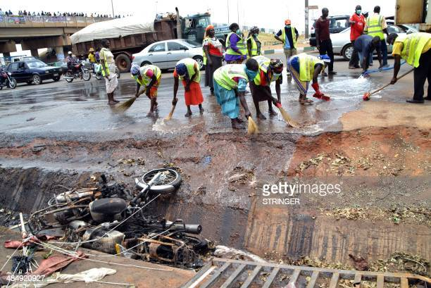 Nigerian workers clean the site of a bomb blast in Abuja on April 15 2014 Nigerian police boosted security across Abuja after a bomb blast ripped...