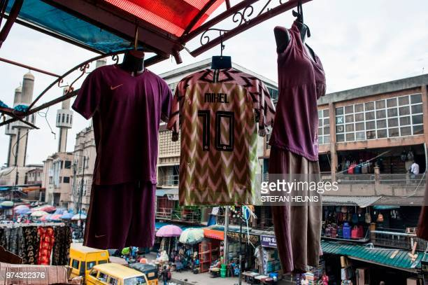 Nigerian World Cup jersey is displayed outside a shop in Balogun Market in Lagos on June 14, 2018. - The Nigeria Super Eagles jersey for the 2018...