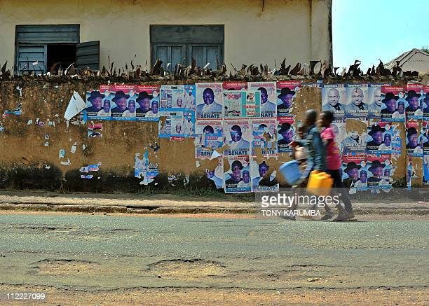 Nigerian young boys walk along a street lined with destroyed postrers advertising Presidential candidate Jonathan Goodluck at Jos the administrative...