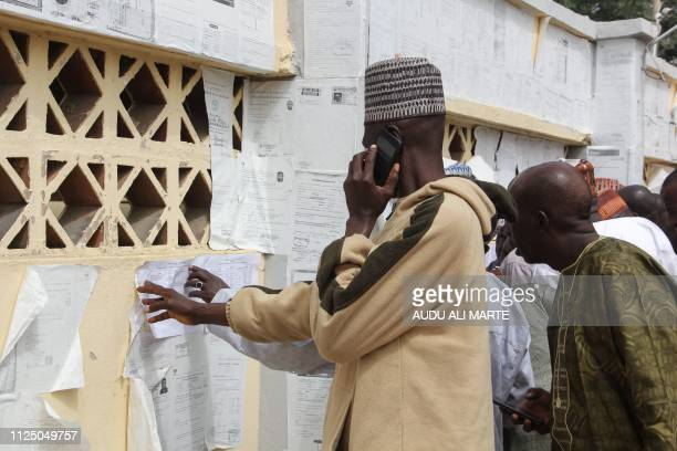 Nigerians check their names against the voters roll in Maiduguri in Borno State in northeastern Nigeria on February 15 2019 Nigeria's presidential...