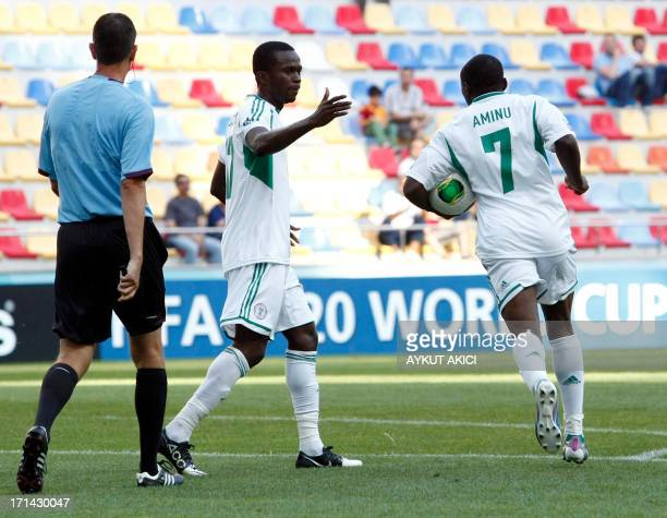 Nigeria's Aminu Umar holds the ball as he celebrates with teammate after scoring during the group stage football match between Cuba and Nigeria at...