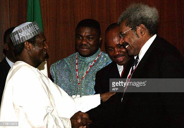 Nigeria's boxing heavyweight champion Samuel Peter views US boxing promoter Donald Don King being greeted by Nigerian President Umaru Yar'Adua as...