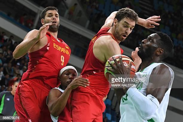 Nigeria's centre Ekene Ibekwe catches the ball as Spain's power forward Felipe Reyes, Nigeria's point guard Josh Akognon and Spain's centre Pau Gasol...