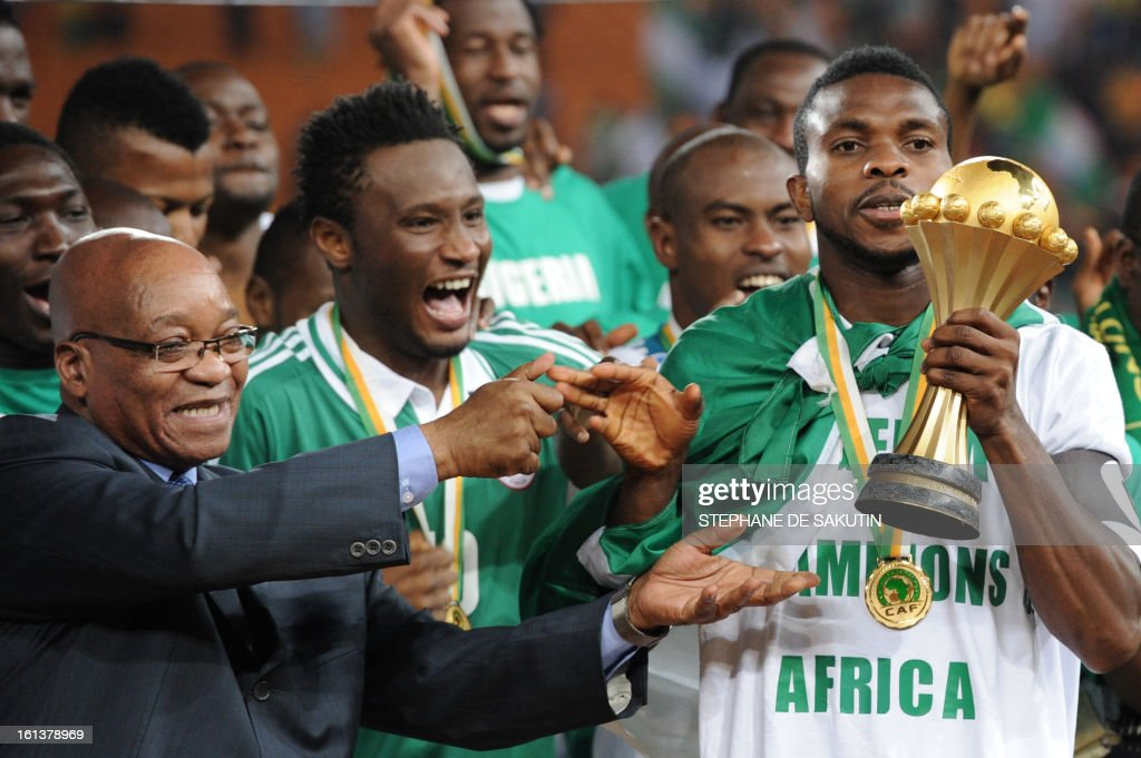Nigeria's defender and team captain Joseph Yobo (R) receives the trophy from South African President Jacob Zuma (L) after Nigeria won the 2013 African Cup of Nations final against Burkina Faso on February 10, 2013 at Soccer City stadium in Johannesburg.