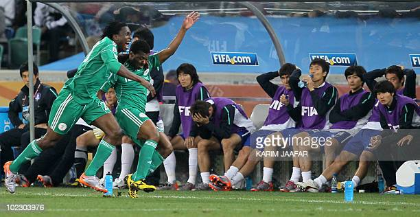 Nigeria's defender Ayodele Adeleye celebrates with midfielder Kalu Uche after the latter scored the team's first goal as South Korean players look on...