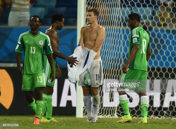 Nigeria's defender Efe Ambrose exchanges jerseys with BosniaHercegovina's forward Edin Dzeko at the end of the Group F football match between Nigeria...