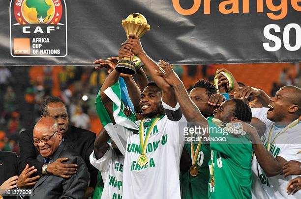 Nigeria's defender Joseph Yobo holds the trophy as he celebrates with teammates South African President Jacob Zuma and Confederation of African...