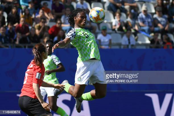 TOPSHOT Nigeria's forward Desire Oparanozie jumps for the ball during the France 2019 Women's World Cup Group A football match between Nigeria and...