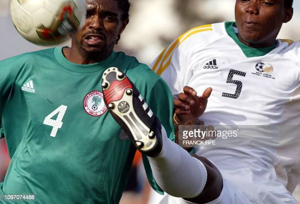 Nigeria's forward Nwankwo Kanu fights for the ball with South African defenders Mabizela Mbulelo 31 January 2004 in Monastir, Tunisia, during their...
