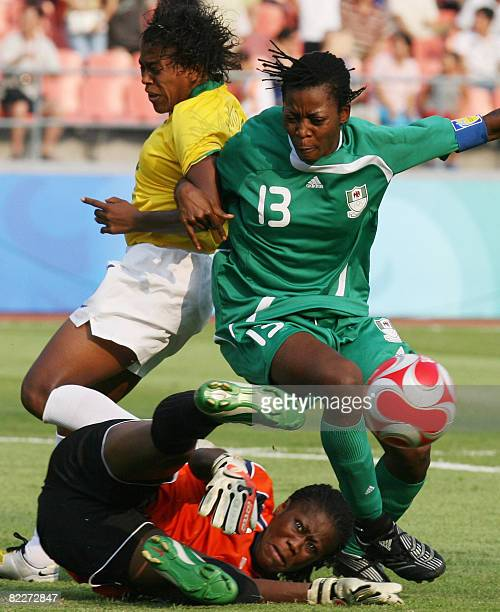 Nigeria's goalkeeper Precious Dede and Christie George vie with Brazil's Maycon at the Worker's Stadium in Beijing during their 2008 Beijing Olympic...