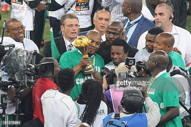 Nigeria's head coach Stephen Keshi poses with the trophy as he celebrates winning the 2013 African Cup of Nations final against Burkina Faso on...