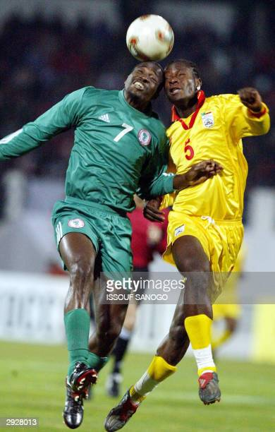 Nigeria's John Utaka and Benin's Damien Chrysostome duel for a high ball, 04 February 2004 in Sfax, during their African Nations Cup match. AFP PHOTO...