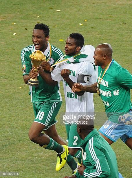 Nigeria's midfielder John Obi Mikel Nigeria's defender Joseph Yobo and Nigeria's goalkeeper Vincent Enyeama hold the trophy as they celebrate winning...