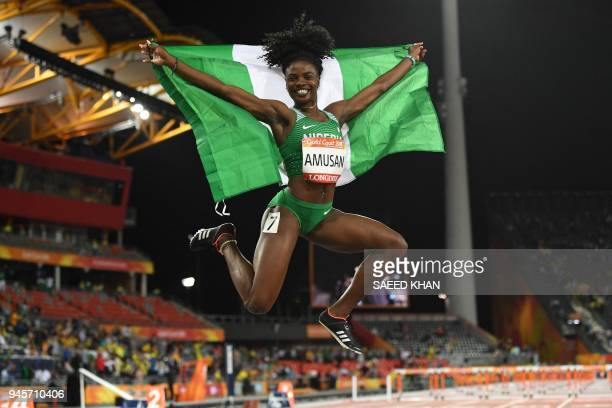 Nigeria's Oluwatobiloba Amusan celebrates with flag after winning the athletics women's 100m hurdles final during the 2018 Gold Coast Commonwealth...