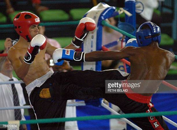 Nigeria's Otteh Happy throws a kick at Tunisian Ahmed Kadaya on his way to victory in their UFC 54 during their Kick Boxing final men match 15 July...