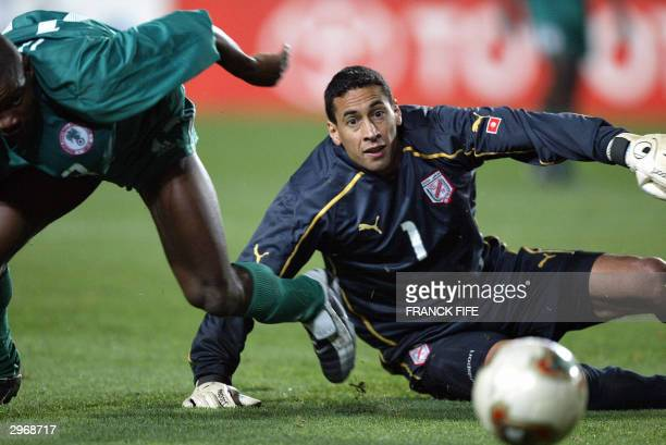 Nigeria's Pius IIkedia challenges Tunisian goalie Ali Boumnijel 11 February 2004 at the Rades stadium during their 2004 African Nations Cup semi...