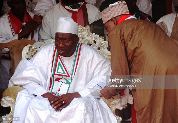 Nigeria's President and candidate for the Peoples Democratic Party Goodluck Jonathan speaks with a campaign aide during a rally in Kano Northern...