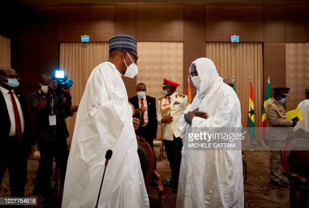 Nigeria's President Muhammadu Buhari and the Imam Mahmoud Dicko , influential leader of the opposition coalition, greet each other after a meeting in...