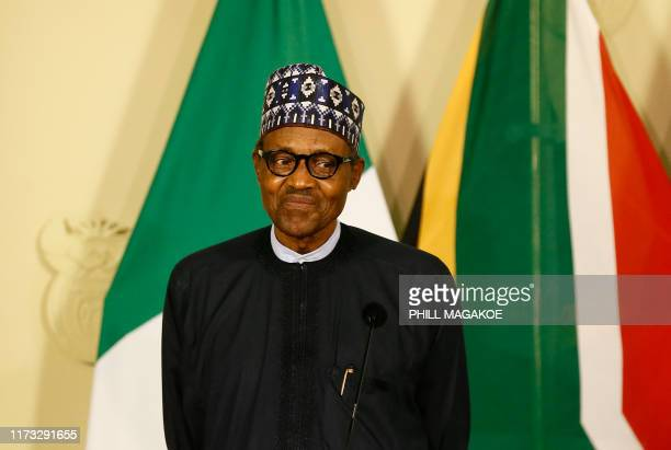 Nigeria's President Muhammadu Buhari reacts while giving a press conference during his official state visit at Union Buildings in Pretoria, on...