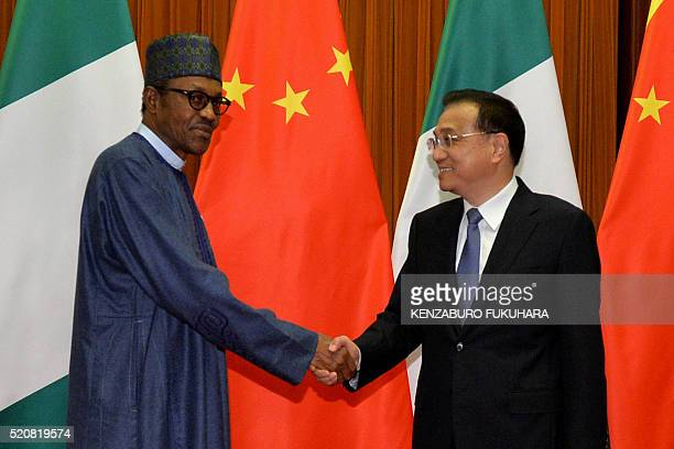 Nigeria's President Muhammadu Buhari shakes hands with Chinese Premier Li Keqiang before their meeting at Great Hall of the People in Beijing on...
