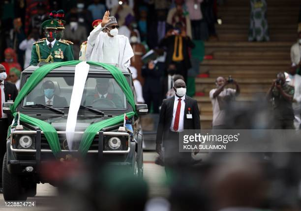 Nigerias President Muhammadu Buhari wave at the crowd as he attends a parade during the countrys 60th Independence Celebration at the Eagles Square...